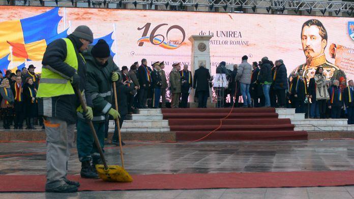 Doi muncitori de la salubritate mătură covorul roșu pe care urmează să vină oficialitățile în Piața Unirii din Focșani. FOTO: Recorder