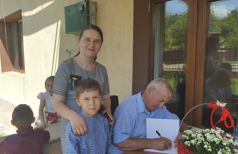 Foto 5: Prof. Budescu dând autograf fiului preotului Iulian George Măciucă