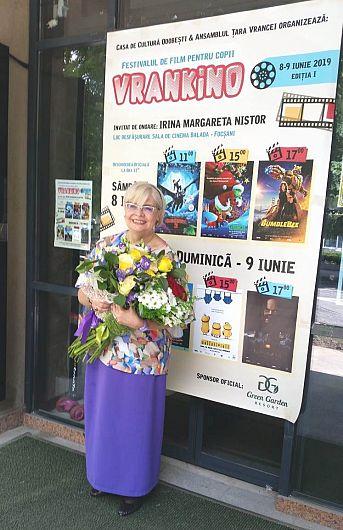 Foto1: Irina Margareta Nistor în fața afișului Festivalului