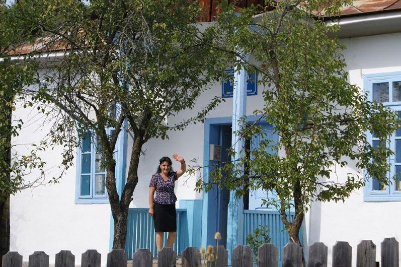 Doamna învățătoare Nina Neagu ne face cu mâna la despărțire din pragul școlii